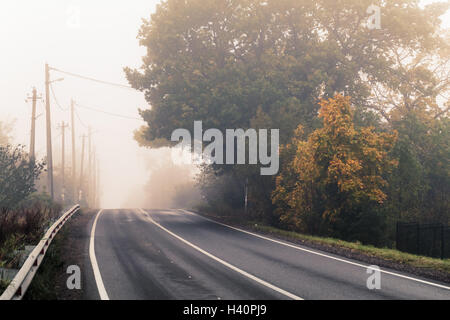 Empty rural highway in autumn foggy morning, stylized photo with warm tonal correction effect, old instagram style filter