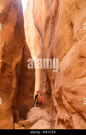 A climbers makes his way through a red rock slot canyon in southern Utah - Stock Photo