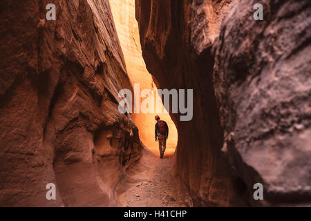 A man canyoneers through a red slot canyon in southern Utah - Stock Photo