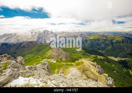 Pordoi pass mountain road and Marmolada mountain range seen from the Sass Pordoi plateau in Dolomites, Italy, Europe - Stock Photo