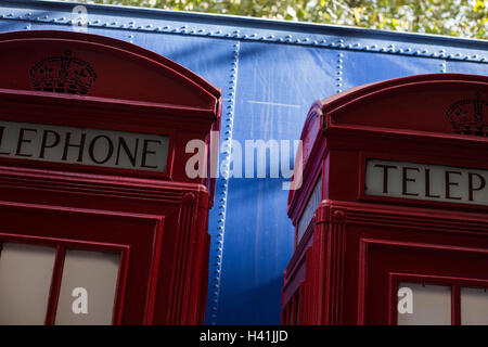 Detail of two traditional red telephone boxes in front of bright blue lorry. - Stock Photo