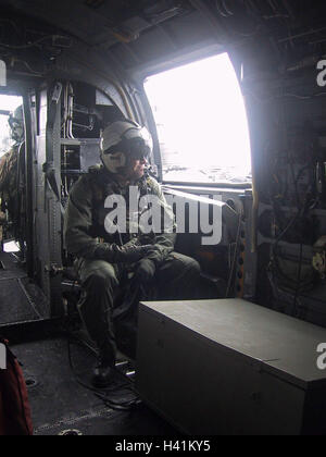 28th January 2003 During Operation Enduring Freedom, a crew member sits at the side door of a U.S. Navy Sea Knight - Stock Photo