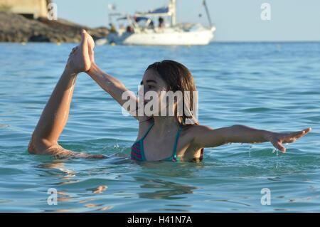 Girl standing in the sea doing standing bow pulling yoga pose - Stock Photo