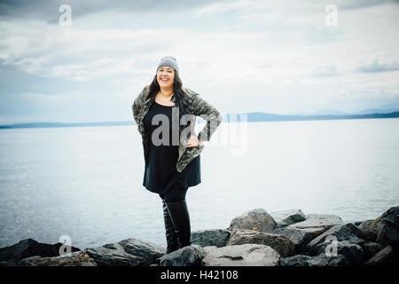 Smiling Mixed Race woman posing on rocks near ocean - Stock Photo