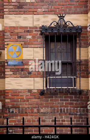An ageing Fallout Shelter sign on an old building in Lower Manhattan, New York. - Stock Photo