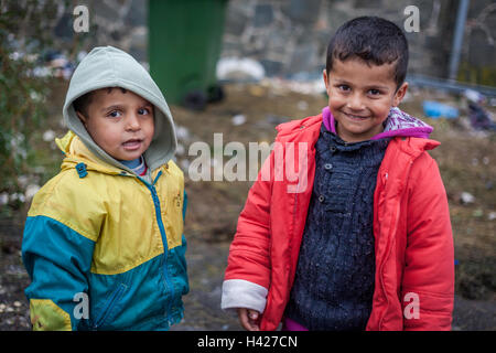 Two child refugees in the refugee camp in Spielfeld, waiting to cross the border between Slovenia and Austria. - Stock Photo