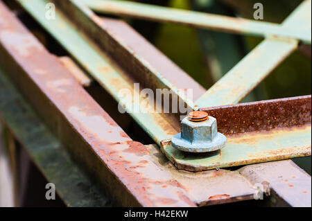 Detail of hexagonal metal screw fastener on corner of partly rusted steel bars and plates. - Stock Photo