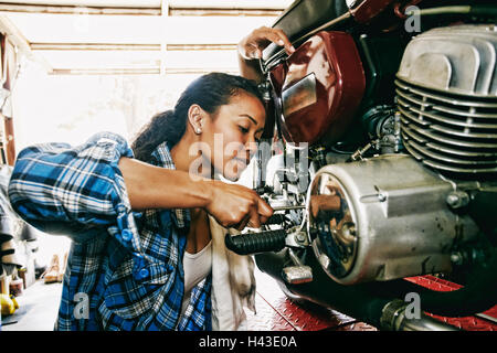 Mixed Race woman repairing motorcycle in garage