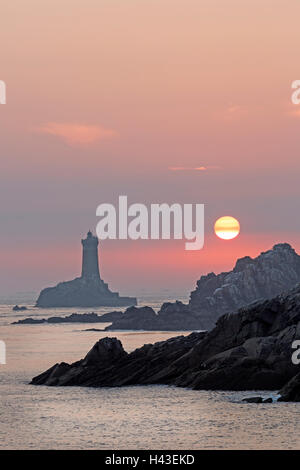 Pointe du Raz with lighthouse at sunset, Sizun, Brittany, France - Stock Photo