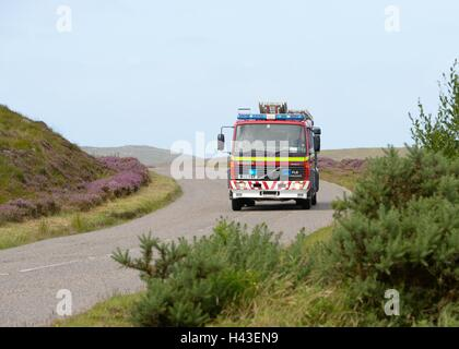 A fire appliance responding to an emergency call in the Scottish Highlands. - Stock Photo