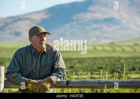 Caucasian farmer wearing gloves leaning on wooden fence