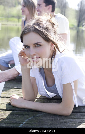 Man, two women, young, happy, wooden jetty, sit, lie, - Stock Photo