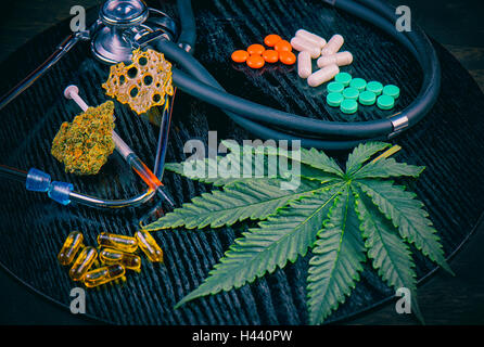 Medical marijuana products vs conventional pills, including cannabis leaf, dried bud, shatter piece, cbd caps and - Stock Photo