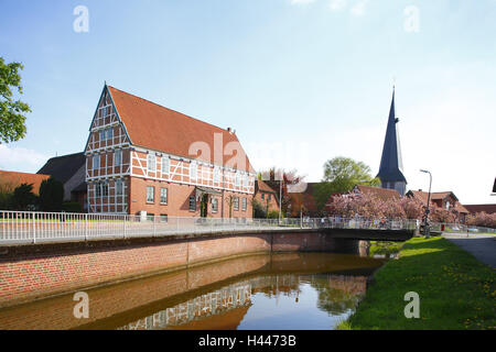 Old country, half-timbered house and church in the channel in Jork-Borstel, - Stock Photo