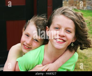 two happy young girls or siblings, sisters posing for camera, piggy back ride - Stock Photo