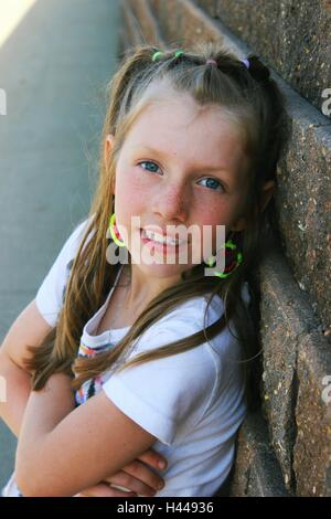 contemporary or modern portrait of a young pretty girl leaning on brick wall smiling - Stock Photo