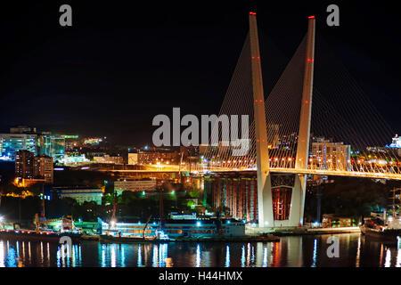 Night view of the bridge in the Russian Vladivostok over the Golden Horn bay - Stock Photo