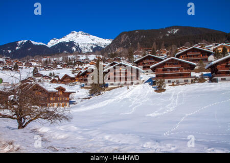Wooden chalets covered by snow in Swiss Alps, Wengen, Switzerland - Stock Photo