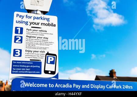 Pay for car parking using mobile sign signs instructions pay and display parking car park sign UK England GB - Stock Photo