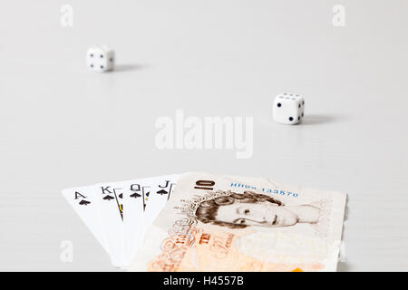 Poker hand with a ten pound note - Stock Photo