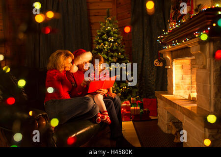 Happy family reading book at home by fireplace in warm and cozy living room on winter day christmastime - Stock Photo