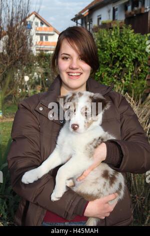 Girls, happy, Australian Shepherd, puppy, hold, half portrait, young animal, mammal, dog, pet, young, animal, young - Stock Photo