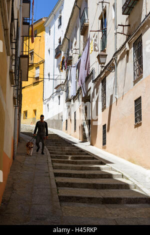 Cuenca, Spain: Main with dog walks down the steps - Stock Photo