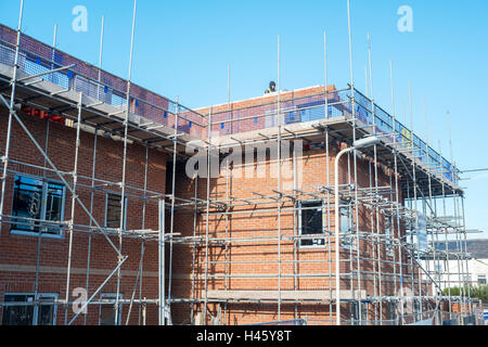 Affordable homes under construction; building covered in scaffolding near completion. UK - Stock Photo
