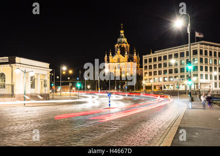 Traffic rushes at night in front of the Uspenski Cathedral at night in Helsinki, Finland capital city. - Stock Photo