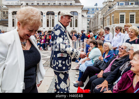 A Pearly King Entertains The Crowd At The Pearly Kings and Queens' Harvest Festival, The Guildhall Yard, London, - Stock Photo