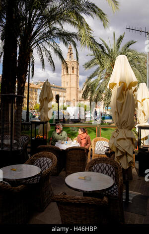 An outdoor cafe in the Reina Place with the Miguelete Tower Valencia - Stock Photo