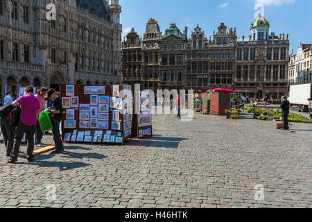 BRUSSELS, BELGIUM - APRIL 5, 2008:  Street vendors sell paintings to tourists in front of guild houses on Grand - Stock Photo