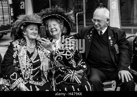 Two Pearly Queens Pose For A Selfie At The Pearly Kings and Queens' Harvest Festival, The Guildhall Yard, London, - Stock Photo
