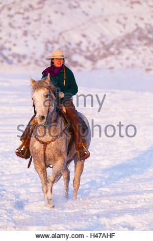 Cowgirl riding on Quarter Horse through snow-covered landscape, - Stock Photo
