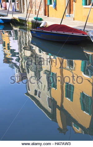 Colorful painted houses reflecting in the calm water of a channel in the lanes on the island Burano, - Stock Photo
