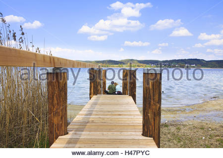 Couple sitting on a jetty at Lake Constance, back view, - Stock Photo