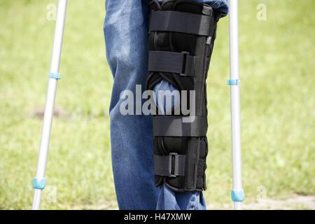 Person, detail, feet, knees, injury, crutches, rail, knee injury, trousers, jeans, bandage, knee prop, bone prop, - Stock Photo