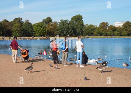 People enjoying warm September weather in Kensington Gardens, London England United Kingdom UK - Stock Photo