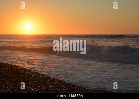 waves crash against the shore with a bright orange sunset - Stock Photo