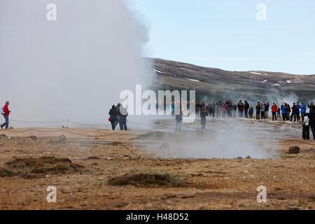 tourists stand around watching the strokkur geyser erupting geysir Iceland - Stock Photo