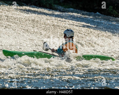Male adult White Water Kayaking along a River Exe Weir on a bright Autumn day. Situated near Exeter in Devon, United - Stock Photo