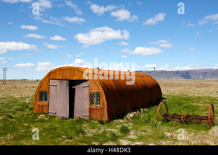 old rusting nissen hut on farmland in Iceland - Stock Photo