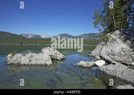 Eibsee with Grainau close Garmisch-Partenkirchen, rock on the east shore, view at Ammergebirge with cross point, - Stock Photo