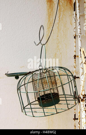 Wall of a house, feed cage, empty, cage, feed dispenser, old, rusty, traces of usage, object photography, nobody, - Stock Photo