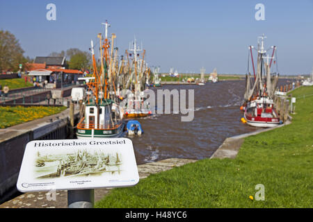 Sign 'Historisches Greetsiel', crab cutter in the harbour of Greetsiel, - Stock Photo