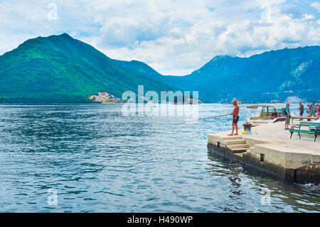 Tourists and locals like to spend their time on the sea promenade: walking, fishing, swimming, Perast - Stock Photo