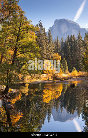 Half Dome and the Merced River surrounded by fall foliage, Yosemite National Park, California, USA. Autumn (October) - Stock Photo