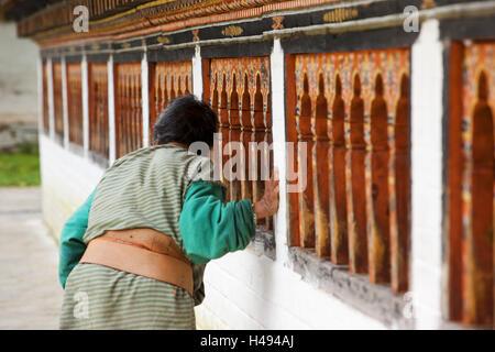 Kingdom of Bhutan, old woman turning prayer mills, - Stock Photo