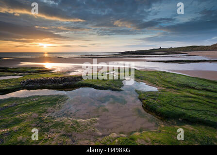 Gorgeous sunrise over Embleton Beach, looking towards Dunstanburgh Castle, Northumberland, England. Spring (May) - Stock Photo