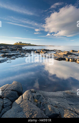 Rocky coastline with rockpools near Dunstanburgh Castle, Craster, Northumberland, England. Spring (April) 2013. - Stock Photo